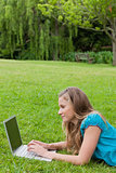 Side view of a young girl working on her laptop while lying on t