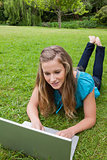 Young girl lying on the grass while raising her legs and using h