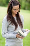Serious young woman reading a book while standing up in a park