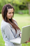 Young relaxed woman holding her laptop while standing in a park