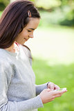 Relaxed young woman sending a text while standing in the country