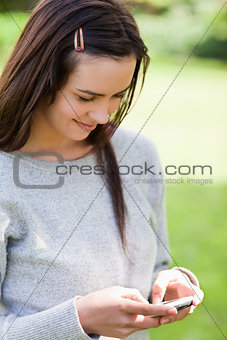 Relaxed young girl sending a text with her mobile phone while st