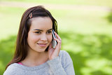 Young relaxed girl talking on the phone while standing in the co