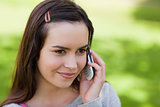 Young relaxed girl talking on the phone in a park
