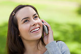 Young smiling woman looking up while talking on the phone