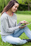 Young smiling woman sitting on the grass in a park while using h