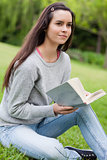 Thoughtful young woman holding a book while sitting on the grass