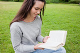Young relaxed girl reading a book while sitting in a public gard