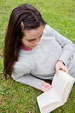 Young woman reading a book while lying on the grass