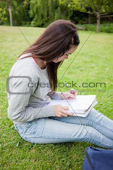 Young serious student sitting in a park while writing on a noteb