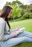 Side view of a young girl sitting on the grass while writing on
