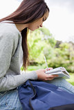 Young smiling student doing her homework in a park