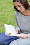 Serious young girl sitting on the grass while reading a book