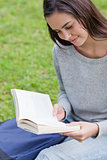 Young relaxed girl sitting in a public garden while reading a bo