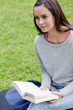 Young calm woman reading a book in a park while looking towards