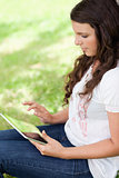 Young woman sitting in the countryside while using her tablet pc