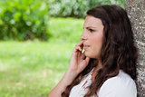 Young serious woman talking on the phone while leaning against a