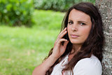 Young serious woman calling with her mobile phone while sitting