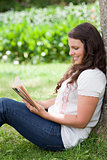 Young smiling woman reading a book while leaning against a tree