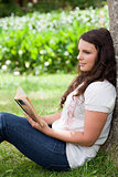 Young thoughtful girl leaning against a tree while reading a boo