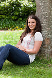 Young smiling woman sitting against a tree with arms crossed