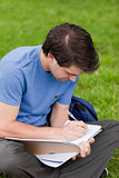 Young student sitting on the grass while writing on his notebook