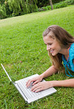 Smiling young woman lying in a park while working on her laptop