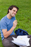 Young smiling man working while sitting on the grass