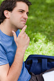 Young man placing his finger on his chin while sitting in a park