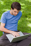 Young serious man working on his laptop while sitting in a park