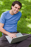 Young smiling man using his laptop while sitting cross-legged