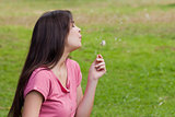 Young relaxed woman blowing a dandelion