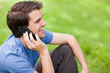 Young man talking on the phone while sitting on the grass