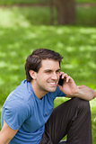 Young smiling man calling with his cellphone while sitting in a 