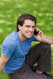 Young happy man using his mobile phone while sitting on the gras