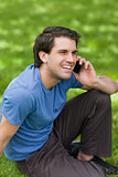 Young man laughing while sitting on the grass and talking on the