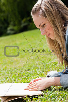 Young blonde girl lying on the grass while reading a book