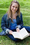 Young girl sitting cross-legged while holding a book and looking