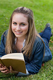 Young happy girl lying on the grass while holding a book and loo