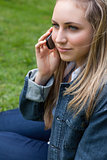 Young blonde woman calling with her mobile phone while sitting i