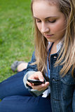 Young girl sending a text while sitting on the grass