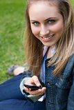 Young blonde girl sitting on the grass while sending a text