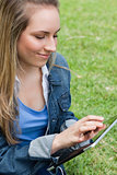 Young peaceful woman using her tablet pc while sitting on the gr