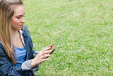 Young serious girl using her tablet pc in the contryside