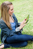 Young attractive blonde girl sitting on the grass while using he