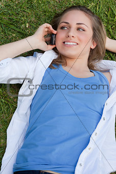 Young smiling girl lying on her back on the grass while calling