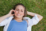 Young smiling blonde girl lying on her back while looking up
