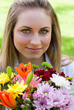 Young relaxed girl holding a bunch of flowers in a public garden