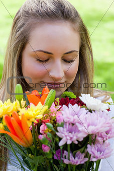 Young blonde girl closing her eyes while smelling a bunch of flo