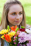 Young relaxed blonde girl holding a bunch of flowers while looki